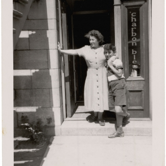 Black-and-white photograph of a woman and a boy standing at the doorstep of a ground floor apartment. The woman has her arm around the son and rests her other arm against the entrance to the apartment.