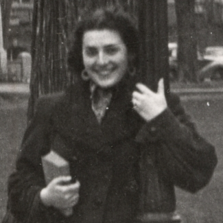 Black-and-white photograph of a woman smiling and leaning against a street light in front of a large field with buildings and cars in the background. She holds a purse and book in her hand.