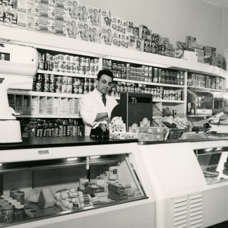 Black-and-white photograph of a man standing behind the cash register of  a large grocery store. He stands in front of a shelf full of food products, and there is a large display food counter in front of him.