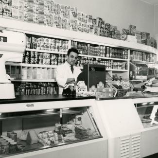 Photo en noir et blanc d'un homme se tenant derrière une caisse enregistreuse dans une grand épicerie. Il se tient devant une étagère remplie de produits et il y a un grand comptoir de présentation devant lui.