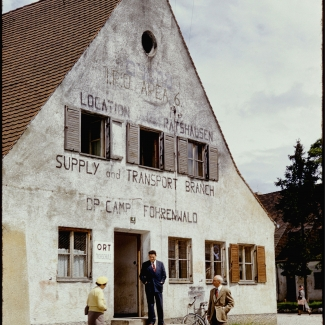 Colour slide of the exterior view of a three-storey building. Three men stand outside the building.
