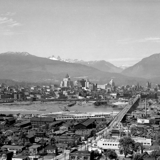 Black-and-white photograph of a bird's eye view of a city. Several buildings are pictured on either side of a river. A bridge connecting the two banks is pictured on the right-hand side of the photo. Several mountain peaks are visible in the background.