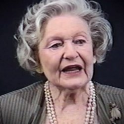 Screenshot of Holocaust survivor Irene Burstyn video testimony. She is sitting in front of a black background, and looking to the left of the camera. The camera shows her face and shoulders.