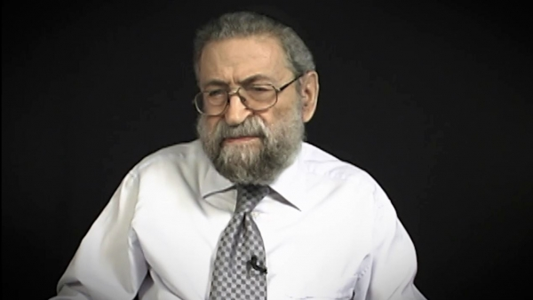 Screenshot of Holocaust survivor Joseph Lazar video testimony. He is sitting in front of a black background, and looking to the left of the camera. The camera shows his face and shoulders