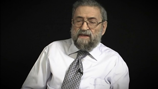 Capture d'écran du témoignage vidéo du survivant de l'Holocauste Joseph Lazar, assis devant un fond noir, et regardant à la gauche de la caméra. Son visage et ses épaules sont visibles à la caméra.
