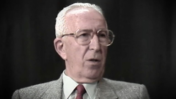 Screenshot of Holocaust survivor Jack Hahn video testimony. He is sitting in front of a dark background, and looking to the right of the camera. The camera shows his face and shoulders.