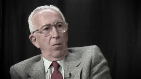 Screenshot of Holocaust survivor Jack Hahn video testimony. He is sitting in front of a dark background, and looking to the right of the camera. The camera shows his face and shoulders