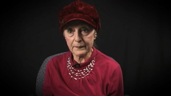 Screenshot of Holocaust survivor Sarah Engelhard video testimony. She is sitting in front of a black background, and looking to the left of the camera. The camera shows her face and shoulders.