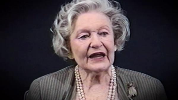 Capture d'écran du témoignage vidéo de la survivante de l'Holocauste Irene Burstyn, assise devant un fond noir, et regardant à la gauche de la caméra. Son visage et ses épaules sont visibles à la caméra.