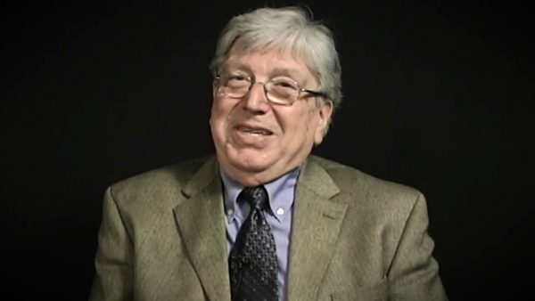 Screenshot of Holocaust survivor Paul Herczeg video testimony. He is sitting in front of a black background, and looking to the left of the camera. The camera shows his face and shoulders.