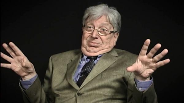Capture d'écran du témoignage vidéo du survivant de l'Holocauste Paul Herczeg, assis devant un fond noir, et regardant à la gauche de la caméra. Son visage et ses épaules sont visibles à la caméra.