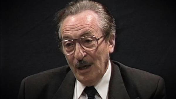 Capture d'écran du témoignage vidéo du survivant de l'Holocauste Michael Kutz, assis devant un fond noir, et regardant à la gauche de la caméra. Son visage et ses épaules sont visibles à la caméra.