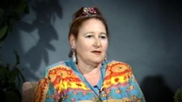 Capture d'écran du témoignage vidéo de la survivante de l'Holocauste Hélène Goldflus, assise devant un fond bleu, et regardant à la droite de la caméra. Son visage et ses épaules sont visibles à la caméra.