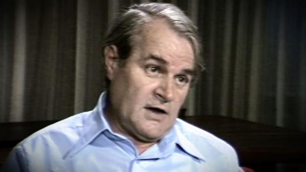 Capture d'écran du témoignage vidéo du survivant de l'Holocauste Aba Beer, assis devant un fond gris, et regardant à la droite de la caméra. Son visage et ses épaules sont visibles à la caméra.