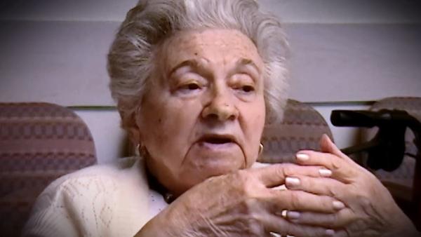 Capture d'écran du témoignage vidéo de la survivante de l'Holocauste Mania Kay, assise et regardant à la droite de la caméra. Son visage et ses épaules sont visibles à la caméra.