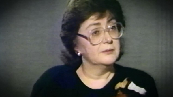 Screenshot of Holocaust survivor Freda Shiel, sitting in front of a grey background, and looking to the right of the camera while recording her video testimony. The camera shows her face and shoulders.