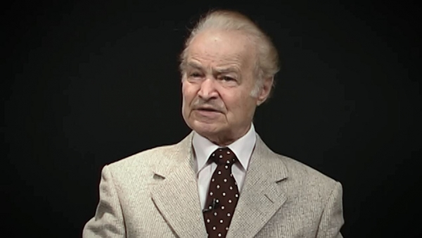 Screenshot of Leon Hirsch, Holocaust survivor, sitting in front of a grey background, and looking to the left of the camera while recording his video testimony. The camera shows his face and shoulders.