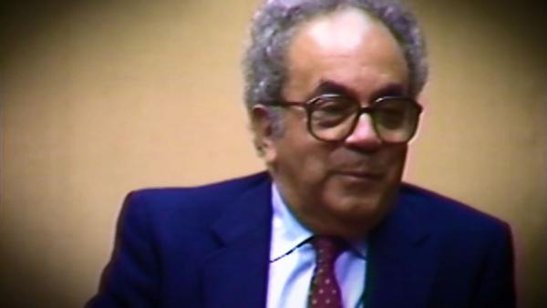Capture d'écran du témoignage vidéo du survivant de l'Holocauste David Shafran, assis devant un fond beige, et regardant à la droite de la caméra. Son visage et ses épaules sont visibles à la caméra.