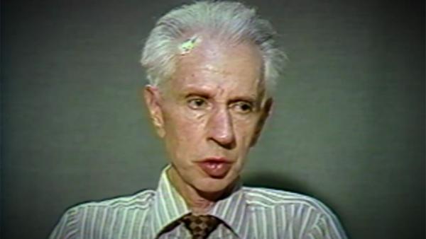 Capture d'écran du témoignage vidéo du survivant de l'Holocauste Stefan Carter, assis devant un fond noir, et regardant à la droite de la caméra. Son visage et ses épaules sont visibles à la caméra.