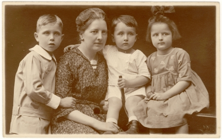 Sepia-toned portrait photograph of a woman with three young children, posing closely together in formal dress.