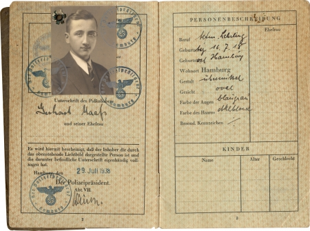 Two pages of a passport with blue stamps and black handwriting. The left page features a black-and-white identity photograph of a young man wearing a suit and tie.