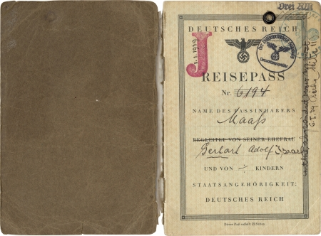 """Two pages of a passport . The passport's first page, on the right, is stamped with a red """"J"""" and date 1/1/1939, and a circular ink stamp from the Police President of Hamburg and another green circular ink stamp. There is handwriting along the border of the page."""