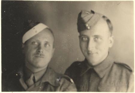 Photo en noir et blanc de deux hommes portant des uniformes militaires souriant à la caméra. L'homme à gauche porte une moustache.