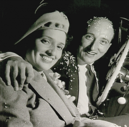 Black-and-white square-shaped photograph of a man and woman sitting together in a car, smiling. The man is covered in confetti and has his arm around the woman.