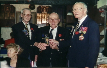 Colour photograph of three elderly men standing together and holding a military medal. The men wear suit jackets adorned in pins and medals.