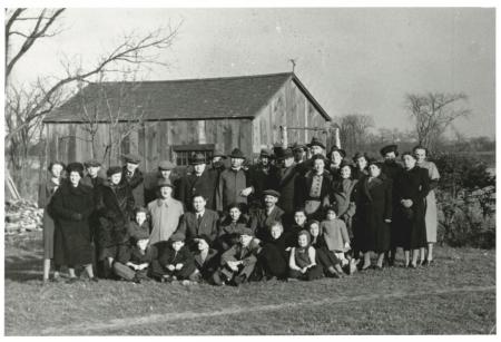 Photo en noir et blanc d'un grand groupe d'environ 35 hommes, femmes et enfants, habillés de manteaux d'hiver et de chapeau, rassemblés ensemble à l'extérieur sur une pelouse. Il y a une grange derrière le groupe en arrière-plan.
