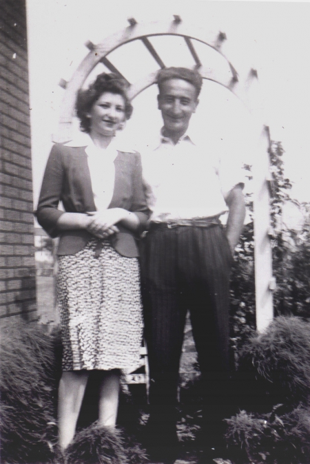 Black-and-white photograph of a man and woman standing together under an arbour outdoors, smiling at the camera. The man has his hands in his pockets.