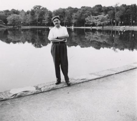 Photo en noir et blanc d'un homme se tenant debout les bras croisés devant un grand étang ou lac. Il porte une chemise à manches courtes, des pantalons noirs et un chapeau. Des arbres entourent le lac en arrière-plan.
