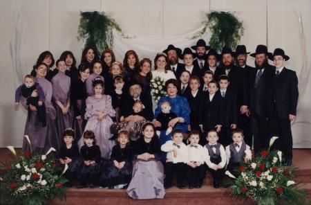 Photo en couleur d'un grand groupe d'environ 30 personnes rassemblés pour une photo de groupe de trois ou quatre rangées, certains sont assis dans la première rangée. Ils sont tous habillés de manière formelle. Les femmes portent des robes et les hommes des complets et des chapeaux. Il y a de grands bouquets de fleurs de chaque côté du groupe.