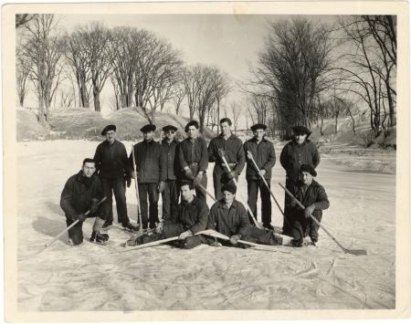 Photo en noir et blanc d'une équipe de hockey de 11 hommes, posant ensemble avec leur bâton de hockey sur la glace d'une patinoire extérieure. Des arbres sont visibles en arrière-plan.