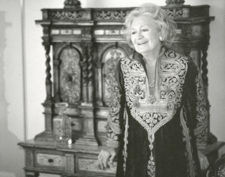 Photo en noir et blanc d'une femme âgée habillée d'une robe brodée, s'appuyant sur une huche en bois sculpté.