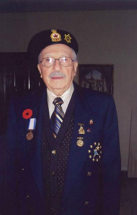 Photo en couleur d'un homme âgé portant un uniforme militaire et souriant à la caméra. Son veston et son béret sont décorés de médailles et d'épinglettes et d'un coquelicot du Jour du souvenir.
