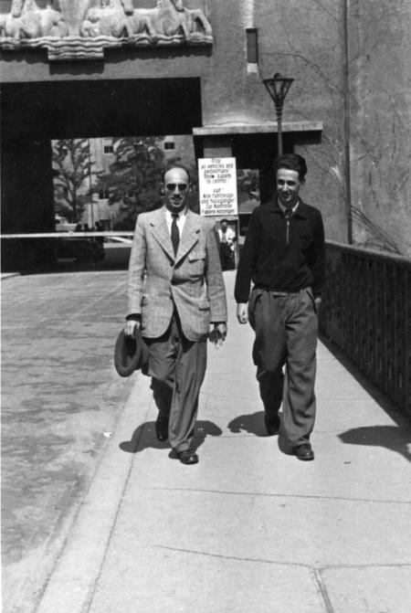 Photo en noir et blanc de deux hommes souriant et marchant vers la caméra sur le trottoir d'un pont. L'homme sur la gauche porte un complet, des verres fumés et tient un chapeau dans sa main droite.
