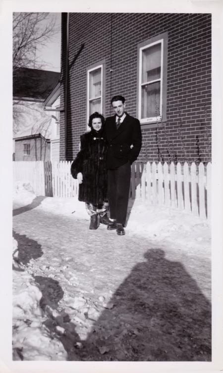 Photo en noir et blanc d'une femme et d'un homme debout ensemble à l'extérieur sur une allée enneigée devant une clôture blanche. La femme porte un manteau de fourrure et l'homme un caban de couleur foncée.