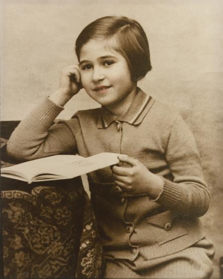 Photo de couleur sépia d'une jeune fille assise à une table sur laquelle il y a une nappe. La fille retient un livre ouvert sur la table d'une main et s'appuie sur l'autre d'une manière pensive. Un léger ton de rose a été ajouté à ses lèvres.