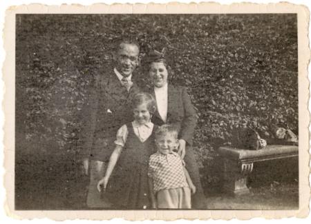 Photo en noir et blanc d'une femme et d'un homme debout ensemble avec deux jeunes enfants à l'extérieur, devant de grandes haies qui prennent tout l'espace en arrière-plan.