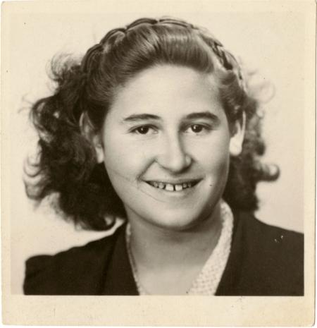 Photo de passeport en noir et blanc d'un jeune adolescente souriant à la caméra. Elle a des cheveux bruns ondulés jusqu'aux épaules.