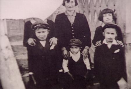 Photo en noir et blanc d'une femme avec cinq enfants se tenant debout, les trois qui sont dans la rangée arrière ont leurs mains sur les épaules de leurs proches. La photo est déchirée dans le coin supérieur gauche de manière à ce que le visage de la personne qui est dans ce coin ne soit pas visible.