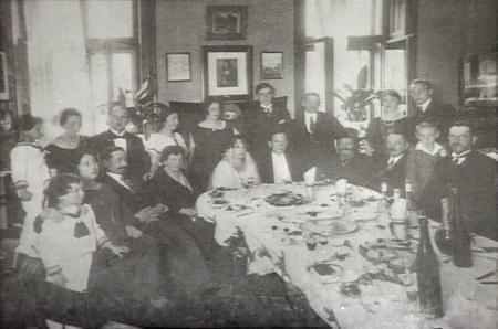 Photo en noir et blanc d'un groupe d'environ 20 personnes assises ensemble autour d'une grande table remplie de plats. Le groupe est habillé de manière formelle et un couple assis à la table semble célébré leur mariage.