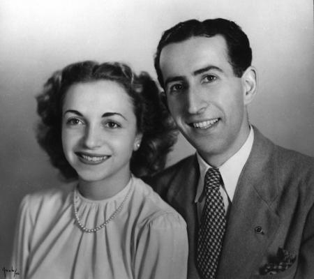 Photo en noir et blanc prise en studio d'un homme et d'une femme assis ensemble et souriant à la caméra. L'homme porte un complet et la femme une blouse avec un collier de perles. Ils ont tous deux des cheveux bruns foncés.