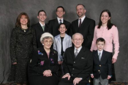 Photo en couleur prise en studio de neuf personnes d'une même famille rassemblées en deux rangées et souriant à la caméra.