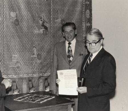 Photo en noir et blanc avec une bordure blanche sur laquelle il y a quatre hommes portant des complets rassemblés debout autour d'une table à l'intérieur. L'homme à droite tient un document et une petite urne.