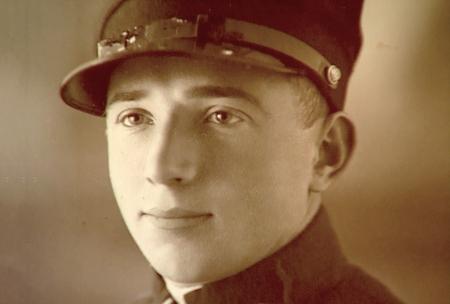 Photo de couleur sépia d'un gros plan du visage d'un homme. L'homme regarde à gauche de la caméra et porte ce qui semble être un uniforme militaire.