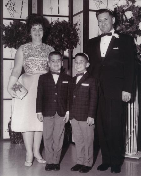 Photo en noir et blanc d'un homme et d'une femme avec leurs deux fils. La famille est vêtue de manière formelle et l'homme ainsi que les garçons portent des complets avec des nœuds papillons et la femme porte une robe.