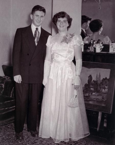 Photo en noir et blanc d'un jeune homme et d'une jeune femme se tenant debout à l'intérieur et souriant ensemble devant un mirroir. La femme porte une longue robe formelle de couleur claire ainsi qu'un petit sac à main et l'homme porte un complet.