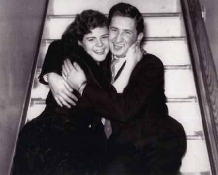 Photo en noir et blanc d'un jeune couple souriant et assis dans les bras l'un de l'autre dans un escalier.